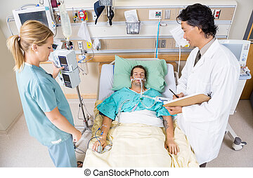 Doctor And Nurse Examining Critical Patient - High angle...