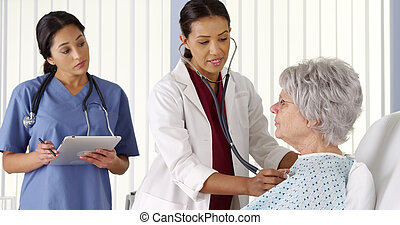 Doctor and nurse listening to elderly woman patient's heart and taking notes