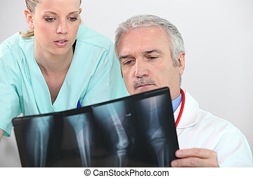 Doctor and nurse looking at an leg xray