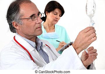 Doctor and nurse preparing IV drip