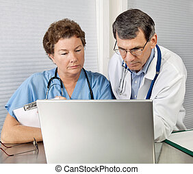 Doctor and Nurse Reviewing on Laptop Computer in Office -...