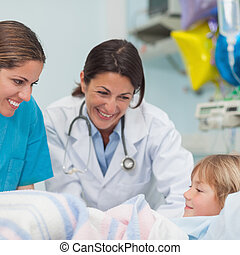 Doctor and nurse smiling to a child in hospital ward