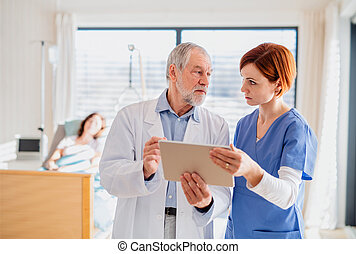 Doctor and nurse with tablet discussing issues in hospital room.