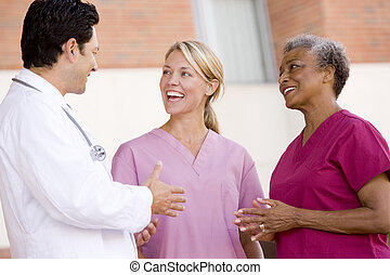 Doctor And Nurses Standing Outside A Hospital