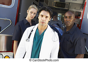 Doctor and paramedics standing in front of an ambulance