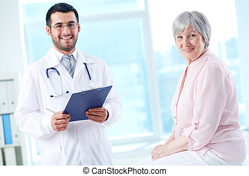 Doctor and patient - Confident doctor with stethoscope and...