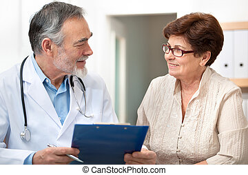Doctor and patient - doctor talking to his female patient at...