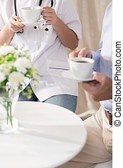 Doctor and patient drinking coffee