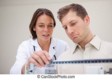 Doctor and patient measuring weight