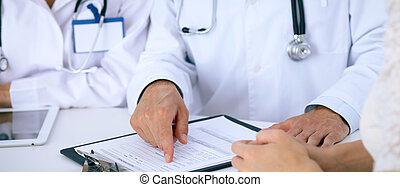 Doctor and  patient talking while sitting at the desk in office. Physician pointing into medical history form. Medicine and health care concept