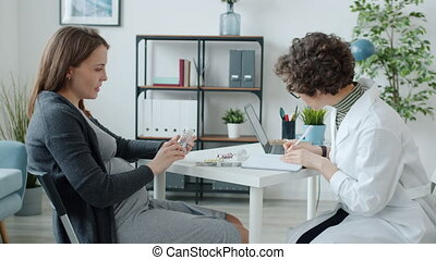Doctor and pregnant young lady are discussing medication looking at pills during appointment in clinic. Medical care and motherhood concept.