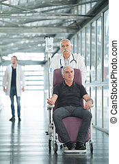 doctor and senior man patient in wheelchair at hospital corridor
