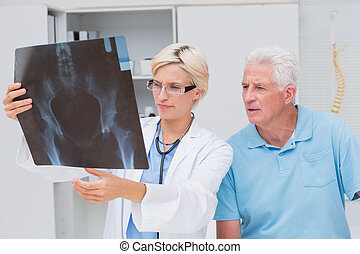 Doctor and senior patient examining x-ray