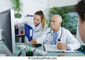 Doctor and student looking at computer screen
