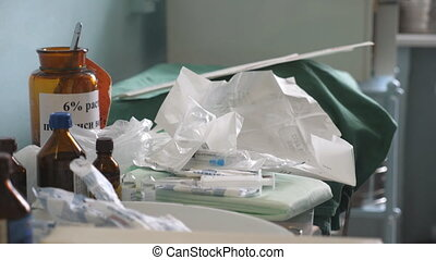 Doctor approaches medical table. Hands of male physician in gloves open the ampoule and puts it on the table. Close up