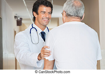 Doctor Assisting Senior Man - Happy young doctor assisting...
