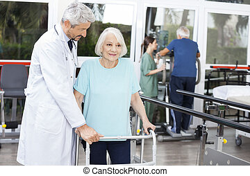 Doctor Assisting Senior Patient With Walker In Fitness Studio