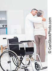 Doctor assisting senior woman to walk with wheelchair in foregro
