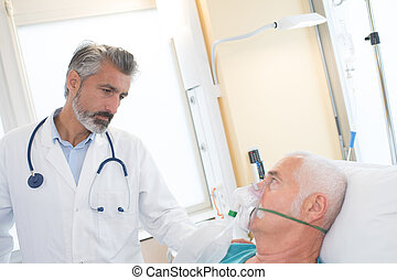 doctor at hospital bedroom with sick patient lying in bed