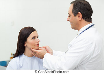 Doctor auscultating the neck of a patient in an examination...