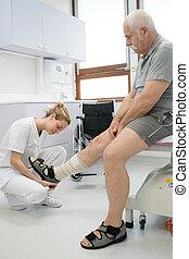 doctor bandaging old mans injured leg