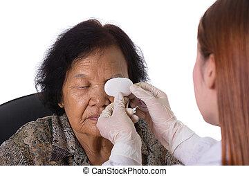 doctor bandaging patient's eye