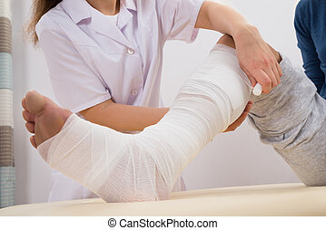 Doctor Bandaging Patient's Leg