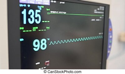 Doctor changes data on the monitor's screen in intensive care unit.