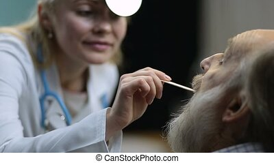 Doctor checking a patient's inflamed throat - Charming...