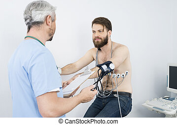 Doctor Checking Blood Pressure Of Patient On Exercise Bike