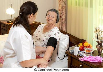 Doctor checking blood pressure to senior woman