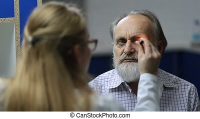 Doctor checking eye symptomatology with flashlight - Young...