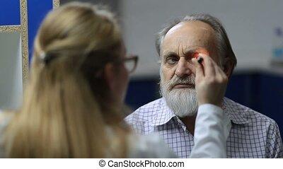Doctor checking eye symptomatology with flashlight - Young...