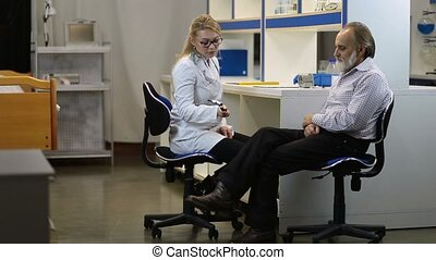 Doctor checking knee reflexes of the patient