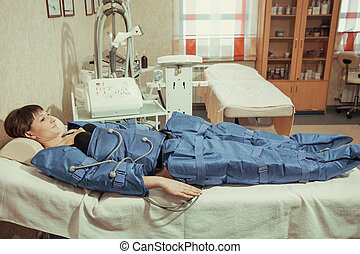 Doctor checking legs pressotherapy machine on woman patient in hospital bed