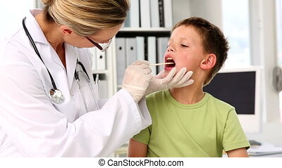 Doctor checking little boys tonsils in her office at the...