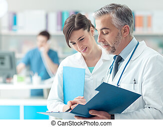 Doctor checking medical records with his assistant