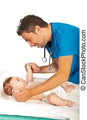 Doctor checking motor skills to baby - Doctor checking motor...