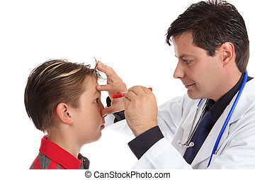 A doctor shines a light into child's eye to check vision ocular health and responsiveness.