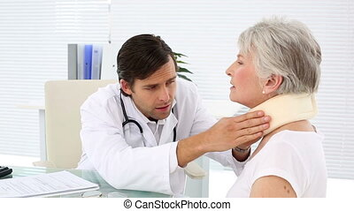 Doctor checking retired patient in neck brace in an office...