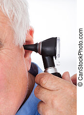 Doctor Checking Senior Man's Ear With Otoscope