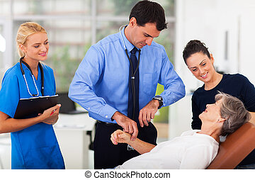 doctor checking senior patient's pulse