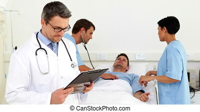 Doctor checking sick patients chart