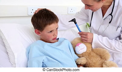 Doctor checking the ears of little boy