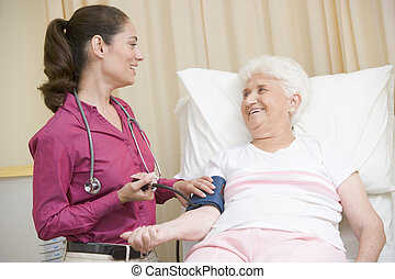 Doctor checking woman\'s blood pressure in exam room smiling