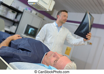 doctor checking xray of a senior patient in hospital