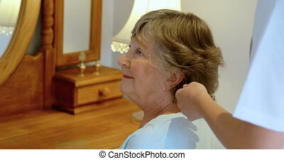 Doctor combing senior woman hair on dressing table 4k -...