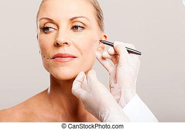 doctor correcting senior woman face
