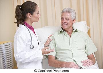 doctor, dar, chequeo, a, hombre, en, habitación de examen, sonriente