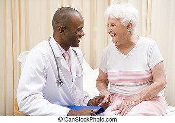 doctor, dar, chequeo, a, mujer, en, habitación de examen, sonriente